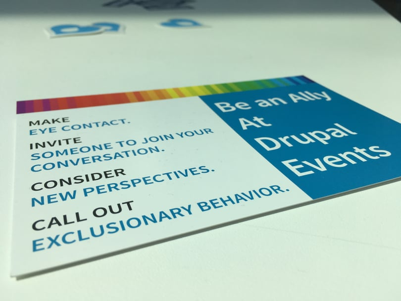 "Flyer put on a table with the text ""Make eye Contact. Invite someone to join the conversation. Consider new perspectives. Call out exclusionary behavior. Be an ally at Drupal events."""