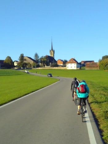 two biking Liipers in front of a sunny landscape with a church